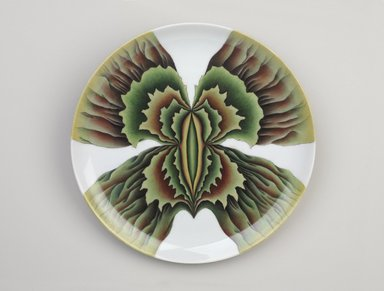 """Judy Chicago (American, born 1939). <em>Aspasia Place Setting</em>, 1974-1979. Runner: Cotton/linen base fabric, woven interface support material (horsehair, wool, and linen), cotton twill tape, silk, stiffened cotton/linen fabric, """"polished cotton"""" fabric, silk thread, metallic cord, cotton, thread Plate: Porcelain with overglaze enamel (China paint), Runner: 52 x 30 in. (132.1 x 76.2 cm). Brooklyn Museum, Gift of The Elizabeth A. Sackler Foundation, 2002.10-PS-11. © artist or artist's estate (Photo: Brooklyn Museum, 2002.10-PS-11_plate_PS9.jpg)"""
