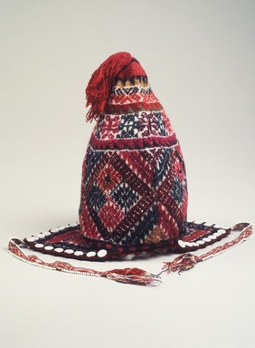 Quechua. <em>Knitted Hat or Ch'ullu</em>, 2002. Alpaca fleece, sheep wool, shell buttons, glass and plastic beads, natural and synthetic dyes, includes ear flaps, tassel, and rim: 13 1/2 x 10 1/4 x 10 1/4 in. (34.3 x 26 x 26 cm). Brooklyn Museum, Frank Sherman Benson Fund, 2002.62.1. Creative Commons-BY (Photo: Brooklyn Museum, 2002.62.1_transp6213.jpg)