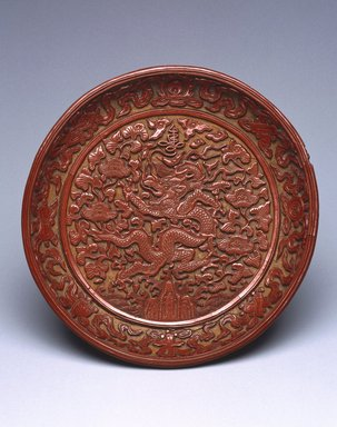 <em>Dish Depicting a Dragon Amongst Foliage</em>, 1522-1566. Carved cinnabar lacquer on wood, diameter: 7 3/8 in. (18.7 cm). Brooklyn Museum, Gift of Patricia Falk, from the Collection of Pauline B. and Myron S. Falk, Jr., 2003.30. Creative Commons-BY (Photo: Brooklyn Museum, 2003.30_SL1.jpg)