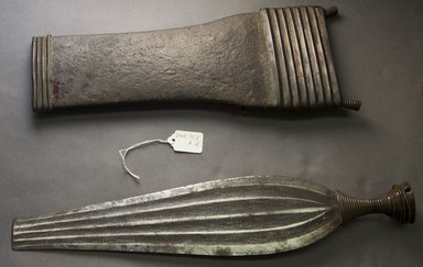Ngbaka. <em>Knife with Sheath</em>, 19th century. Iron, copper alloy, wood, skin, 18 1/2 x 6 1/2 x 1 3/4 in. (47 x 16.5 x 4.4 cm). Brooklyn Museum, Gift of Dorothea and Leo Rabkin, 2004.75.5a-b. Creative Commons-BY (Photo: Brooklyn Museum, 2004.75.5a-b_side_PS10.jpg)