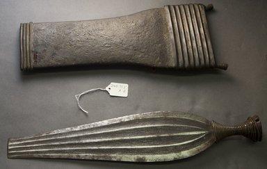 Ngbaka. <em>Knife with Sheath</em>, 19th century. Iron, copper alloy, wood, skin, 18 1/2 x 6 1/2 x 1 3/4 in. (47 x 16.5 x 4.4 cm). Brooklyn Museum, Gift of Dorothea and Leo Rabkin, 2004.75.5a-b. Creative Commons-BY (Photo: Brooklyn Museum, 2004.75.5a-b_side_PS10.jpg)