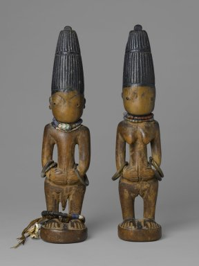 Yorùbá artist. <em>Pair of twin figures (Ère Ìbejì)</em>, late 19th-early 20th century. Wood, pigment, glass, metal, cotton, cowrie shells, a: 12 × 3 × 5 in. (30.5 × 7.6 × 12.7 cm). Brooklyn Museum, Gift of the Coltrera Collection, 2010.22.1a-b. Creative Commons-BY (Photo: Brooklyn Museum, 2010.22.1a-b_front_PS6.jpg)