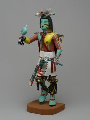 Henry Shelton (born 1929). <em>Kachina Doll</em>, 1960-1970. Cottonwood root, acrylic paint, yarn,metal bells, feathers, leather, cotton, 13 1/2 x 4 1/2 x 5 1/2 in. (34.3 x 11.4 x 14 cm). Brooklyn Museum, Gift of Edith and Hershel Samuels, 2010.6.12. Creative Commons-BY (Photo: Brooklyn Museum, 2010.6.12_front_PS2.jpg)