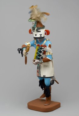 Henry Shelton (born 1929). <em>Kachina Doll</em>, 1960-1970. Cottonwood root, acrylic pigment, yarn, feathers, shell, hide, cotton, beads, 16 1/2 x 4 x 8 in. (41.9 x 10.2 x 20.3 cm). Brooklyn Museum, Gift of Edith and Hershel Samuels, 2010.6.9. Creative Commons-BY (Photo: Brooklyn Museum, 2010.6.9_front_PS2.jpg)
