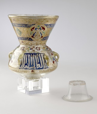 <em>Mosque Lamp</em>, 13th-14th century. Colorless glass; blue, green, red, yellow, and white enamels; and gold;  free blown, applied, enameled, and gilded; tooled on the pontil, includes base, now detached: 12 x 8 in. (30.5 x 20.3 cm). Brooklyn Museum, Bequest of William H. Herriman, 21.484. Creative Commons-BY (Photo: Brooklyn Museum, 21.484_during_treatment_view1_PS9.jpg)
