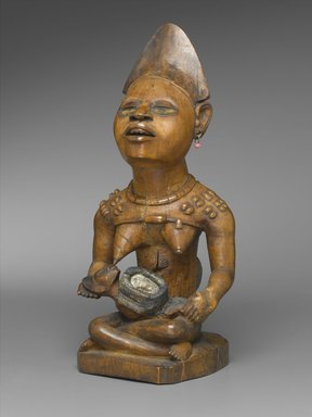 Yombe artist. <em>Figure of Mother and Child (Phemba)</em>, 19th century. Wood, glass, upholstery studs, metal, metal and glass buttons, resin, 11 x 5 x 4 1/2 in. (27.9 x 12.7 x 11.4 cm). Brooklyn Museum, Museum Expedition 1922, Robert B. Woodward Memorial Fund, 22.1138. Creative Commons-BY (Photo: Brooklyn Museum, 22.1138_threequarter_PS2.jpg)