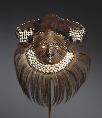 Kuba (Bushoong subgroup) artist. <em>Mask (Mwaash aMbooy)</em>, late 19th or early 20th century. Rawhide, paint, plant fibers, textile, cowrie shells, glass, wood, monkey pelt, feathers, 22 x 20 x 18 in. (55.9 x 50.8 x 45.7 cm). Brooklyn Museum, Museum Expedition 1922, Robert B. Woodward Memorial Fund, 22.1582. Creative Commons-BY (Photo: Brooklyn Museum, 22.1582_edited_SL1.jpg)