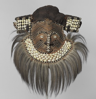 Kuba (Bushoong subgroup) artist. <em>Mask (Mwaash aMbooy)</em>, late 19th or early 20th century. Rawhide, paint, plant fibers, textile, cowrie shells, glass, wood, monkey pelt, feathers, 22 x 20 x 18 in. (55.9 x 50.8 x 45.7 cm). Brooklyn Museum, Museum Expedition 1922, Robert B. Woodward Memorial Fund, 22.1582. Creative Commons-BY (Photo: , 22.1582_overall_PS9.jpg)