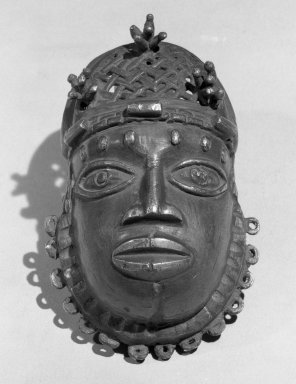 Edo. <em>Pendant Mask (Uhunmwun-ekue)</em>, 19th century. Copper alloy, 4 15/16 × 2 15/16 in. (12.5 × 7.5 cm). Brooklyn Museum, Museum Expedition 1923, Purchased with funds given by Frederic B. Pratt and Frank L. Babbott, 23.280. Creative Commons-BY (Photo: Brooklyn Museum, 23.280_acetate_bw.jpg)