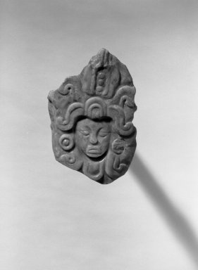 <em>Pendant in Form of Human Head</em>. Jadeite, 2 1/4 x 3/8 x 3 1/2 in. (5.7 x 1 x 8.9 cm). Brooklyn Museum, Frank L. Babbott Fund, 36.268. Creative Commons-BY (Photo: Brooklyn Museum, 36.268_acetate_bw.jpg)