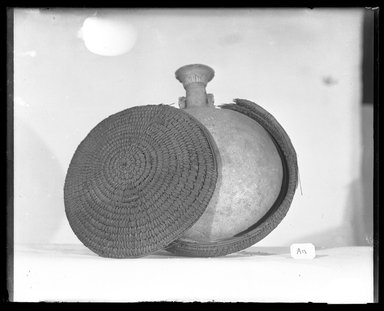 <em>Pilgrim Flask Enclosed in a Basket</em>, 664-332 B.C.E. Faience, fibers Brooklyn Museum, Charles Edwin Wilbour Fund, 37.338E. Creative Commons-BY (Photo: Brooklyn Museum, 37.338E_NegF_SL4.jpg)
