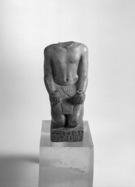 <em>Kneeling Statue of Nesbanebdjedet</em>, ca. 755-730 B.C.E. Steatite or faience, glaze, 5 3/8 x 1 7/8 x 3 1/4 in. (13.6 x 4.8 x 8.3 cm). Brooklyn Museum, Charles Edwin Wilbour Fund, 37.344E. Creative Commons-BY (Photo: Brooklyn Museum, 37.344E_front_bw_SL1.jpg)