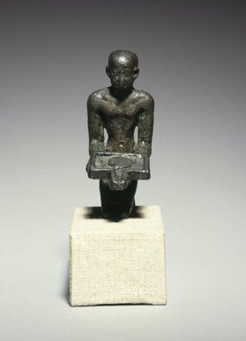<em>Priest with an Offering Table</em>, ca. 1539 B.C.E. or later. Bronze, 2 1/2 x 13/16 x 1 7/16 in. (6.4 x 2.1 x 3.7 cm). Brooklyn Museum, Charles Edwin Wilbour Fund, 37.362E. Creative Commons-BY (Photo: Brooklyn Museum, 37.362E_front_SL1.jpg)
