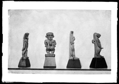 <em>Bes Amulet</em>, ca. 1075-656 B.C.E. Faience, 1 5/8 × 9/16 × 3/8 in. (4.2 × 1.4 × 0.9 cm). Brooklyn Museum, Charles Edwin Wilbour Fund, 37.924E. Creative Commons-BY (Photo: , 37.924E_37.937E_37.988_37.1083E_GrpB_SL4.jpg)