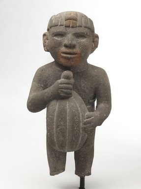 Aztec. <em>Man Carrying a Cacao Pod</em>, 1440-1521. Volcanic stone, traces of red pigment, 14 1/4 x 7 x 7 1/2in. (36.2 x 17.8 x 19.1cm). Brooklyn Museum, Museum Collection Fund, 40.16. Creative Commons-BY (Photo: Brooklyn Museum, 40.16_front_PS9.jpg)