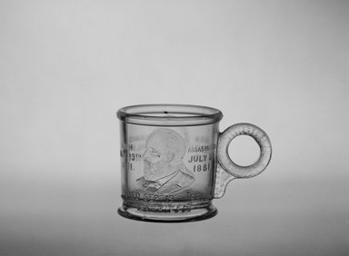 <em>Mug (Abraham Lincoln & James Garfield)</em>, ca. 1881. Glass, 2 5/8 x 3 7/8 x 2 5/8 in. (6.7 x 9.8 x 6.7 cm). Brooklyn Museum, Gift of Mrs. William Greig Walker by subscription, 40.182. Creative Commons-BY (Photo: Brooklyn Museum, 40.182_bw.jpg)