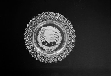 <em>Plate (George Dewey)</em>, ca. 1899. Glass, 3/4 x 5 1/2 x 5 1/2 in. (1.9 x 14 x 14 cm). Brooklyn Museum, Gift of Mrs. William Greig Walker by subscription, 40.185. Creative Commons-BY (Photo: Brooklyn Museum, 40.185_bw.jpg)