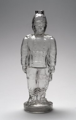 American. <em>Bottle, Figure of Theodore Roosevelt</em>, 1909. Glass, 11 1/8 x 4 x 3 1/4 in. (28.3 x 10.2 x 8.3 cm). Brooklyn Museum, Gift of Mrs. William Greig Walker by subscription, 40.276. Creative Commons-BY (Photo: Brooklyn Museum, 40.276.jpg)