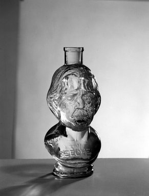 American. <em>Bottle, Bust of Henry Ward Beecher</em>, 1887. Glass, 6 3/4 x 3 x 3 in. (17.1 x 7.6 x 7.6 cm). Brooklyn Museum, Gift of Mrs. William Greig Walker by subscription, 40.279. Creative Commons-BY (Photo: Brooklyn Museum, 40.279_acetate_bw.jpg)