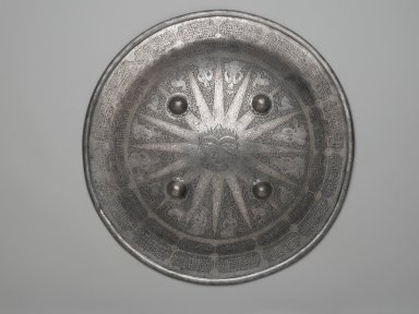 <em>Shield with Arabic Inscription and Signs of the Zodiac</em>, 19th century. Iron alloy (steel), etched and overlaid with silver and gold; fabric lining, Diam. 18 5/8 in. (47.3 cm). Brooklyn Museum, Gift of Percy C. Madeira, Jr., 42.245.2. Creative Commons-BY (Photo: Brooklyn Museum, 42.245.2_PS2.jpg)