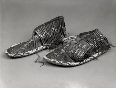 Klikitat. <em>Pair of Embroidered Moccasins</em>, ca 1870s. Buffalo calfskin, porcupine quills, beads, horsehair, woodpecker feathers, tin, 3 15/16 x 11 7/16 x 3 15/16 in. (10 x 29.1 x 10 cm). Brooklyn Museum, Gift of Edna Ebling, 44.203a-b. Creative Commons-BY (Photo: Brooklyn Museum, 44.203a-b_bw.jpg)
