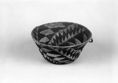 Pomo. <em>Coiled Basket with spiralling triangle patterns</em>. Clam shell, acorn woodpecker feather, quail feather, bulrush, sedge root, 5 7/8 x 12 1/16 in.  (15.0 x 30.7 cm). Brooklyn Museum, Gift of Pratt Institute, 46.136.2. Creative Commons-BY (Photo: Brooklyn Museum, 46.136.2_view1_bw.jpg)