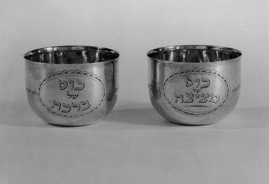 Hester Bateman (English, active in London, 1774-1789). <em>Jewish Ceremonial Wine Cup, One of Pair</em>, 1785-1786 with late 19th-century inscriptions. Silver, 1 3/4 x 2 7/16 x 2 7/16 in. (4.4 x 6.2 x 6.2 cm). Brooklyn Museum, Ella C. Woodward Memorial Fund, 51.110.1. Creative Commons-BY (Photo: , 51.110.1_51.110.2_bw.jpg)