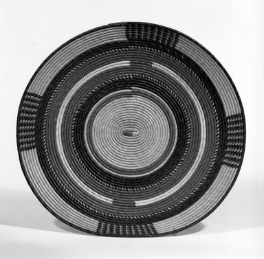 Hausa. <em>Flat Coiled Basketry Lid for a Pot</em>, early 20th century. Vegetable fiber, diam: 14 in. (35.4 cm). Brooklyn Museum, Gift of John W. Vandercook, 51.140.24. Creative Commons-BY (Photo: Brooklyn Museum, 51.140.24_bw.jpg)