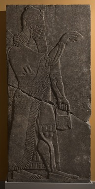 Assyrian. <em>Apkallu-figure with Armlets</em>, ca. 883-859 B.C.E. Gypsum stone, pigment, 89 3/8 x 42 1/8 in. (227 x 107 cm). Brooklyn Museum, Purchased with funds given by Hagop Kevorkian and the Kevorkian Foundation, 55.145. Creative Commons-BY (Photo: Brooklyn Museum, 55.145_at_PS11.jpg)