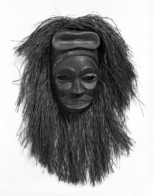Ibibio. <em>Ekpo Society Mask with Fringe Attachment</em>, early 20th century. Wood, raffia or palm fiber, 11 1/2 x 7 1/2 x 4 1/4 in. (29.3 x 19.0 x 10.8 cm). Brooklyn Museum, Gift of Arturo and Paul Peralta-Ramos, 56.6.11. Creative Commons-BY (Photo: Brooklyn Museum, 56.6.11_bw.jpg)
