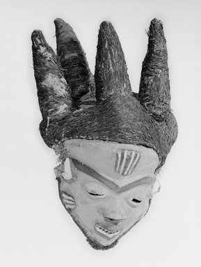 Pende (Western). <em>Mask (Mbuya) of Chief (Phumbu)</em>, late 19th-early 20th century. Wood, pigment, raffia, fiber, 17 5/16 x 11 in.  (44.0 x 27.9 cm). Brooklyn Museum, Gift of Arturo and Paul Peralta-Ramos, 56.6.4. Creative Commons-BY (Photo: Brooklyn Museum, 56.6.4_bw_SL1.jpg)