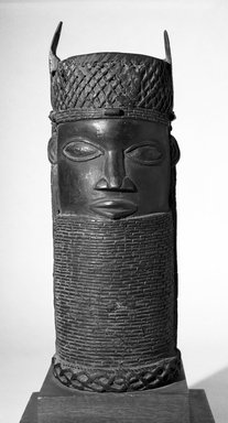 Edo. <em>Benin Head</em>, early 20th century. Copper alloy, 14 15/16 × 5 11/16 in. (38 × 14.5 cm). Brooklyn Museum, Gift of Arturo and Paul Peralta-Ramos, 56.6.66. Creative Commons-BY (Photo: Brooklyn Museum, 56.6.66_bw.jpg)