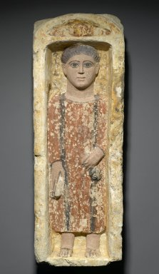 Coptic. <em>Funerary Stela with Boy Standing in a Niche</em>, 4th-5th century C.E. Limestone, ancient and modern paint in ochre, dark terracotta, brown, black and flesh-tone, 27 9/16 x 9 5/8 x 6 1/2 in. (70 x 24.5 x 16.5 cm). Brooklyn Museum, Charles Edwin Wilbour Fund, 58.129. Creative Commons-BY (Photo: Brooklyn Museum, 58.129_PS2.jpg)