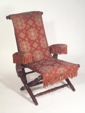 George Jacob Hunzinger (American, born Germany, 1835-1898). <em>Reclining Armchair</em>, patented February 6, 1866. Walnut, various woods, original fringe, late 19th century second show cover, original upholstery retained below on armrests Brooklyn Museum, Bequest of Elsie Patchen Halstead, 60.133.2. Creative Commons-BY (Photo: Brooklyn Museum, 60.133.2.jpg)