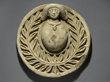 <em>Roundel with Human Head</em>, 20th century (probably). Nummulitic limestone, pigment, 3 15/16 x Diam. 15 3/16 in. (10 x 38.5 cm). Brooklyn Museum, Gift of  Louis Beck and Jerome M. Eisenberg, 60.212. Creative Commons-BY (Photo: Brooklyn Museum, 60.212_PS2.jpg)