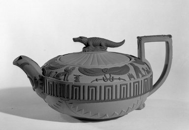 "Josiah Wedgwood & Sons Ltd. (founded 1759). <em>Teapot</em>, ca. 1810. Teapot; ""rosso anitco"" red tinted stoneware with black relief ornamentation; compressed ball form with curved spout and square handle with incurving outer profile, both decorated with black relief ornaments; round lid with black crocodile finial; upper section of body decorated with black hieroglyph relief band; middle section with black symmetrical band; lower section with molded curved zigzag pattern; pot raised on low circular foot