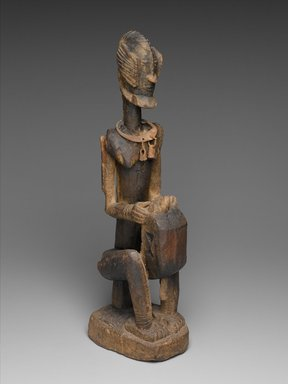 Dogon. <em>Figure of a Seated Musician (Koro Player)</em>, late 18th century. Wood, iron, 22 x 7 x 4 1/4 in. (55.8 x 17.7 x 10.8 cm). Brooklyn Museum, Frank L. Babbott Fund, 61.2. Creative Commons-BY (Photo: Brooklyn Museum, 61.2_threequarter_PS2.jpg)