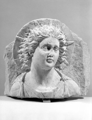 <em>Head of Helios in High Relief Against a Pedimental Background</em>, 3rd century C.E. Limestone, 9 11/16 × 11 in. (24.6 × 28 cm). Brooklyn Museum, Charles Edwin Wilbour Fund, 62.148. Creative Commons-BY (Photo: Brooklyn Museum, 62.148_acetate_bw.jpg)