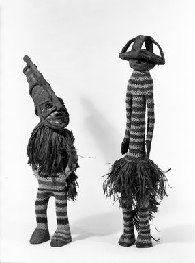 Chokwe. <em>Costumed Dance Figure (Cikunza)</em>, second half 19th century. Net, cotton, raffia fiber, wood, beaten bark, 31 1/2 x 9 1/2 in. (80.0 x 24.0 cm). Brooklyn Museum, Charles Stewart Smith Memorial Fund, 63.55.4. Creative Commons-BY (Photo: , 63.55.3_63.55.4_bw.jpg)