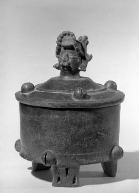 Maya. <em>Cylindrical Tripod Vessel and Cover</em>, 300-600 C.E. Ceramic, dark brown glossy slip, 9 5/8 x 7 3/16 x 7 3/16 in. (24.5 x 18.3 x 18.3 cm). Brooklyn Museum, A. Augustus Healy Fund, 64.163.1. Creative Commons-BY (Photo: Brooklyn Museum, 64.163.1_acetate_bw.jpg)