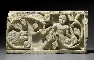 Coptic. <em>Recarved Plant Scroll with Human Figure and Lion Head</em>, 20th century (copy). Limestone, 9 5/8 x 18 1/2 x 3 7/8 in. (24.5 x 47 x 9.8 cm). Brooklyn Museum, Charles Edwin Wilbour Fund, 67.176.2. Creative Commons-BY (Photo: Brooklyn Museum, 67.176.2_PS2.jpg)