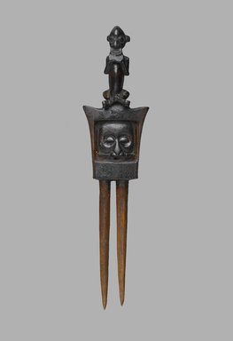 Yaka. <em>Comb with Face, Lizard and Cross-legged Figure (Yisanuna)</em>, late 19th or early 20th century. Wood, 5 3/4 x 1 1/2 x 1/2 in. (14.6 x 3.8 x 1.3 cm). Brooklyn Museum, Bequest of Laura L. Barnes, 67.25.34. Creative Commons-BY (Photo: Brooklyn Museum, 67.25.34_front_PS2.jpg)