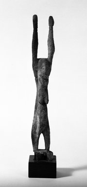 Dogon. <em>Female Figure of a Nommo</em>, 15th-17th century?. Wood, accumulated materials, 14 3/4 x 2 1/2 x 2 in. (37.5 x 6.5 x 5.1 cm). Brooklyn Museum, Gift of Lester Wunderman, 70.178.3. Creative Commons-BY (Photo: Brooklyn Museum, 70.178.3_bw.jpg)