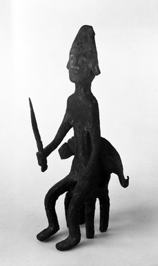 Bamana. <em>Figure of a Seated Male (Gwan)</em>, late 19th-early 20th century. Wrought iron, 8 3/4 x 4 x 4 1/2 in. (22.2 x 10.2 x 11.4 cm). Brooklyn Museum, Gift of Elliot Picket, 70.72.7. Creative Commons-BY (Photo: Brooklyn Museum, 70.72.7_bw.jpg)
