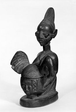 Yorùbá. <em>Kneeling Female Figure Holding Bowl with Face</em>, late 19th or early 20th century. Wood, applied materials, 12 x bowl: 3 x lid:  5 1/2 in. (30.0 x 7.5 x 14.0 cm). Brooklyn Museum, Gift of Dr. and Mrs. Abbott A. Lippman, 71.177.4a-b. Creative Commons-BY (Photo: Brooklyn Museum, 71.177.4a-b_bw.jpg)