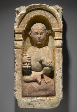 Coptic. <em>Funerary Stela with Boy Seated in a Niche</em>, 4th-5th century C.E. Limestone, ancient and modern paint, 26 9/16 x 12 5/8 x 6 3/16 in. (67.5 x 32 x 15.7 cm). Brooklyn Museum, Charles Edwin Wilbour Fund, 71.39.2. Creative Commons-BY (Photo: Brooklyn Museum, 71.39.2_PS1.jpg)