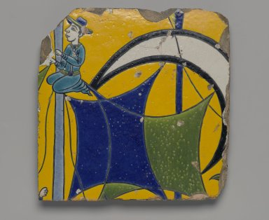 <em>Tile Fragment Depicting a Sailor on the Mast of a Ship</em>, first half of 17th century. Ceramic; fritware, painted in yellow, turquoise, cobalt blue, green, black, opaque white, and light grayish blue glazes with manganese purple in the cuerda seca (dry-cord) technique, 9 7/16 x 9 7/16 in. (24 x 24 cm). Brooklyn Museum, Gift of Mr. and Mrs. Charles K. Wilkinson, 71.49.4. Creative Commons-BY (Photo: Brooklyn Museum, 71.49.4_PS2.jpg)