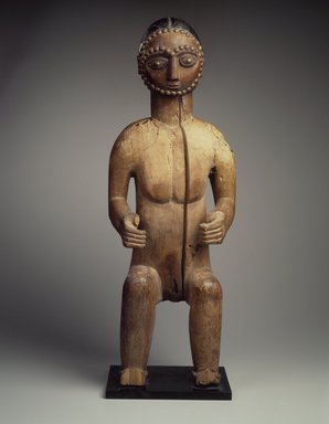 Possibly Wobe. <em>Seated Male Figure</em>, late 19th-early 20th century. Wood, metal studs, metal base, height (with base): 28 3/4 x 10 x 7 in. (73 x 25.4 x 17.8 cm). Brooklyn Museum, Gift of Fernandez Arman to the Jennie Simpson Educational Collection of African Art, 72.102.6. Creative Commons-BY (Photo: Brooklyn Museum, 72.102.6.jpg)