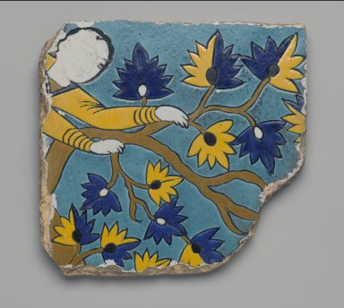 <em>Cuerda Seca Tile Fragment Depicting Youth Climbing a Tree</em>, first half of the 17th century. Ceramic; fritware, painted in yellow, turquoise, cobalt blue, black, opaque white, and ochre-brown glazes with manganese purple in the cuerda seca (dry-cord)