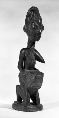 Yorùbá. <em>A Kneeling Female Figure Holding a Bowl for Kola Nuts</em>, late 19th or early 20th century. Wood, h: 19 in. (48.2 cm). Brooklyn Museum, Gift of Mr. and Mrs. John A. Friede, 73.107.10. Creative Commons-BY (Photo: Brooklyn Museum, 73.107.10_bw.jpg)